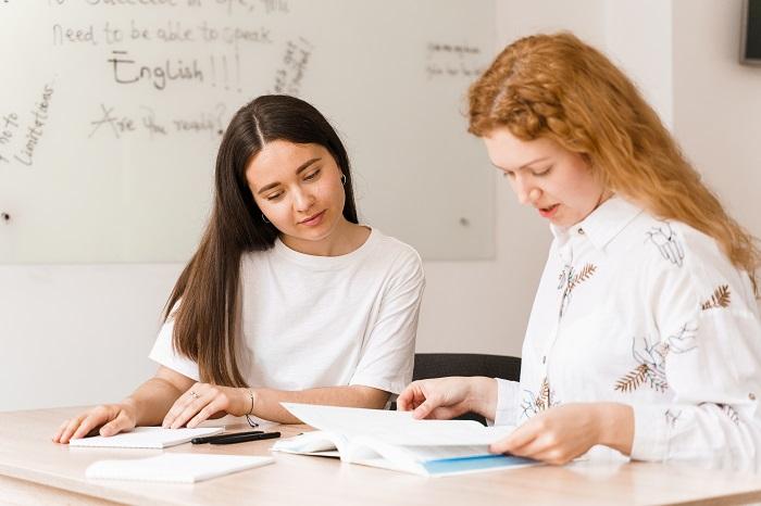 teacher english asks student white class 2 girls student answers teacher